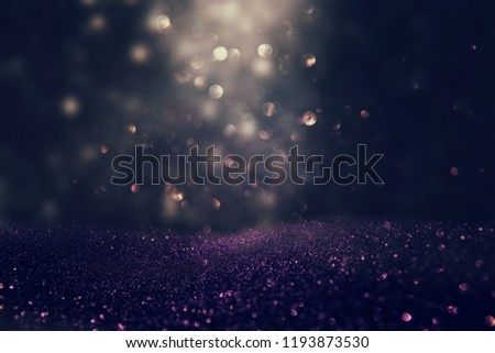glitter vintage lights background. black, gold and purple. de-focused