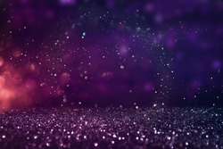 glitter vintage lights background. gold, purple and black. de-focused.