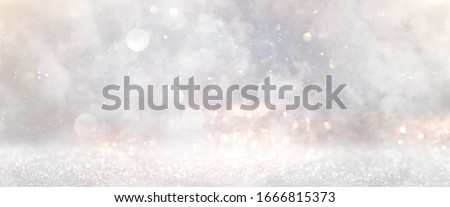 glitter vintage lights background. gold, silver and white. de-focused
