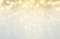 glitter vintage lights background. silver, gold and white. de-focused