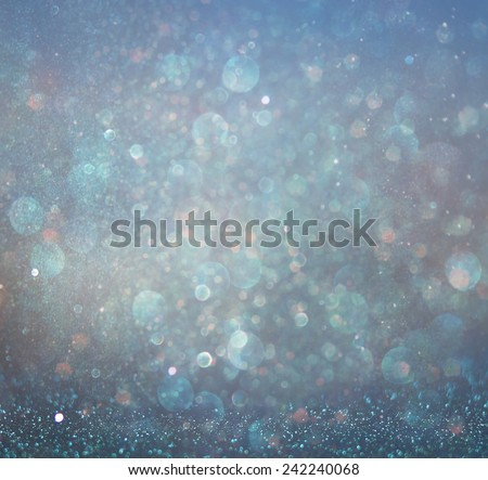glitter vintage lights background with light burst . silver, blue and white. de-focused.
