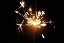 Glittering burning sparkler on black background