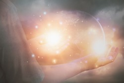 Glittering light shine through hand women,who raise hands,to pray for God blessing,planet and sunset background mind sanctification,concept pure spirit and spirituality,Element image furnished by NASA