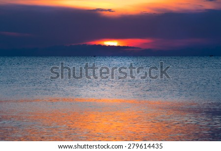 Glittering sea and calmly wave at sunrise, a little tidal. Sun just come up. Dazzling reflection from sunlight on sea surface.