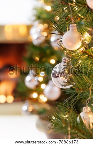 Glittering silver and white Christmas tree decorations by a warm fire