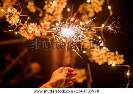 Glittering sparklers against the background of spring flowers of trees. Spring time.