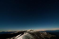 Glittering stars above snowy autumn mountain ridges and city lights