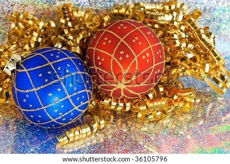 Glittery Christmas ornaments and curled ribbon on sparkling background