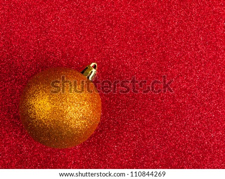 Glittery gold bauble of red glitter background - Christmas, festive
