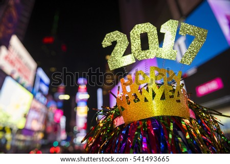 Glittery 2017 Happy New Year message with celebration tinsel flying on novelty party hat in Times Square, New York City
