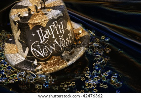 Glittery new year's hat with streamers and confetti shot on artsy background - stock photo