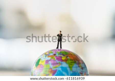 Global and Business Concept. Businessman miniature figure standing on mini world ball model. #611816939