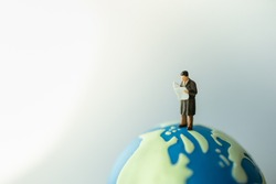 Global Business and Information Concept. Businessman miniature figure people standing and reading a newspaper on mini world ball with copy spcace.