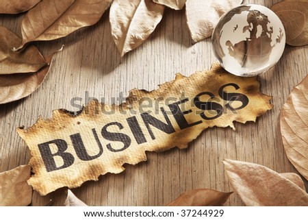 Global business concept using printed word on burnt paper along with compass and golden key, surrounded by dry leaf