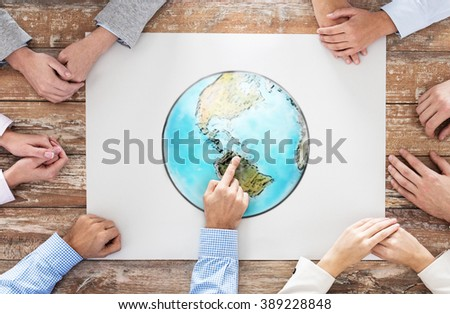 global business, people and team work concept - close up of hands on table pointing finger to earth globe picture in office