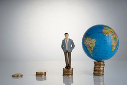 Global capitalism economy lead by successful entrepreneur. Globe, business man maniature on top of stacked coins.  capitalism