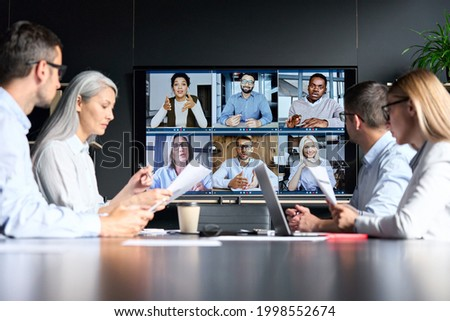 Global corporation online videoconference in meeting room with diverse people sitting in modern office and multicultural multiethnic colleagues on big screen monitor. Business technologies concept.