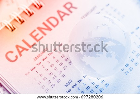 Global date and time or time zone concept : Etched world map on a surface of a clear crystal globe with longitude and latitude lines, put over a mulberry paper calendar with North pole facing up. #697280206