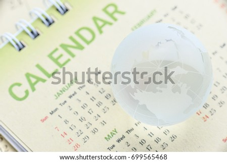 Global date and time or time zone concept : Etched world map on a surface of a clear crystal globe with longitude and latitude lines, put over a mulberry paper calendar with North pole facing up. #699565468