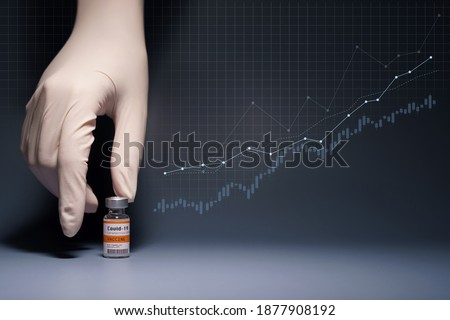 Global economy recovery after Covid 19 Vaccination success concept. Hands of a researcher in medical gloves pick up a Coronavirus Vaccine vial with stock index chart rising up in the background.