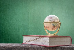 Global education, study aboard, international educational academic program for student concept with world globe, textbook and black school teacher chalkboard background with copy space