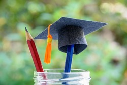 Global education success / graduate study aborad program concept : Black graduation cap or a mortarboard, blue and red pencils in a bottle, depicts achievement in higher mba learning course in academy