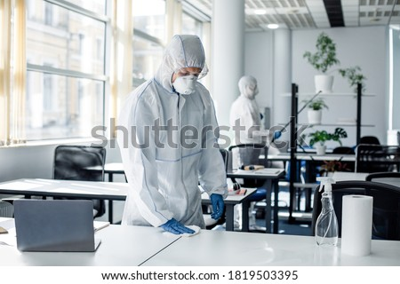 Global epidemic of covid-19 and disinfection of office for return to work of workers. People in hazmat suits, goggles and masks cleaning furniture in interior, copy space