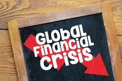 GLOBAL FINANCIAL CRISIS. The word financial crisis written on blackboard. Economic and financial crisis concept. World financial crisis. Top view.