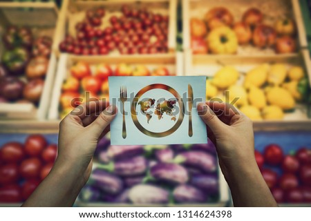 Global hunger issue, food supply problem. Hands holds a paper message as world map in a plate with knife and fork over market shelves. International starvation metaphor, famine after drought season. Сток-фото ©