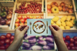 Global hunger issue, water supply problem. Hands holding a paper sheet with world map in a plate with knife and fork icon over market shelves background. International craving and starvation metaphor.