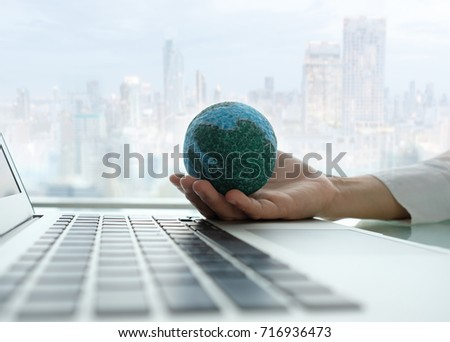 global of technology and business concept. globe on hand and laptop computer with business city background.