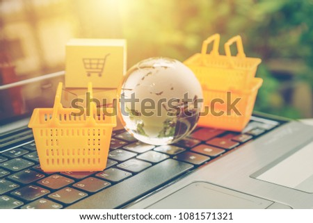 Global or worldwide online shopping / retail ecommerce and delivery service concept : Baskets, a globe map on a laptop, depicts consumers purchase or order products from suppliers or digital stores. #1081571321