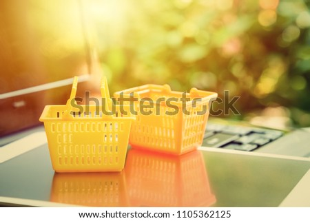Global or worldwide online shopping / retail ecommerce and delivery service concept : Grocery baskets on a laptop, depicts consumers purchase or order products from online suppliers or digital stores. #1105362125