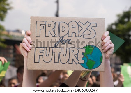 Global strike for planet, students protesting during fridays for future. Hands and posters up to the sky