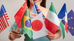 Global travel. Diplomatic relationship. Happy woman holding many international hand flags isolated on neutral. Visa office. Ethnic friendship. Exchange students