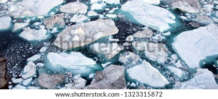 Global Warming and Climate Change - Icebergs from melting glacier in icefjord in Ilulissat, Greenland. Aerial photo of arctic nature iceberg and ice landscape. Unesco World Heritage Site.