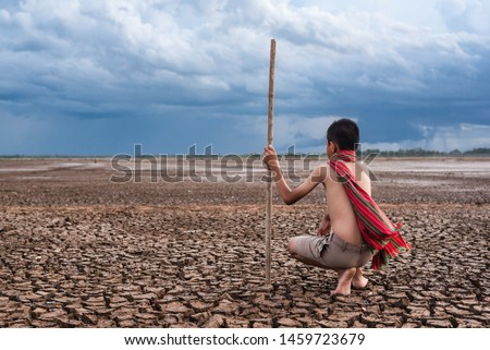 Global warming and water crisis, Boy looking on drought land.Climate Change