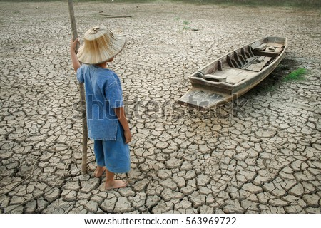 Global warming, Children with boat on cracked earth after the climate change  #563969722