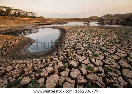 Global warming concept. Climate change and drought land.Deep cracks earth in the red land as a symbol of hot climate and drought.Brown dry soil or desert cracked ground texture background,land arid ea