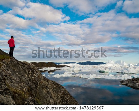 Global warming -Greenland Iceberg landscape of Ilulissat icefjord with giant icebergs. Icebergs from melting glacier. Arctic nature heavily affected by climate change. Person tourist looking at view