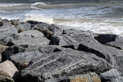 Global Warming sea defences to prevent sea level rises damaging coastal paths and railway. Made of 100,000 tons of Norwegian Granite placed on beaches by barge and crane. at Bexhill, East Sussex