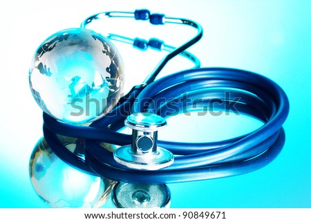 Globe and stethoscope on blue background