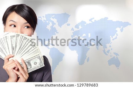 Globe business concept - happy business woman with earned dollar bills us money with world map background, asian beauty model