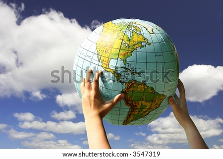 globe in the child's hands on the cloudy sky background