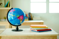 Globe on desk.Pinewood table.Shelves with colorful books.Background.Planet Earth and map.Geography lesson.