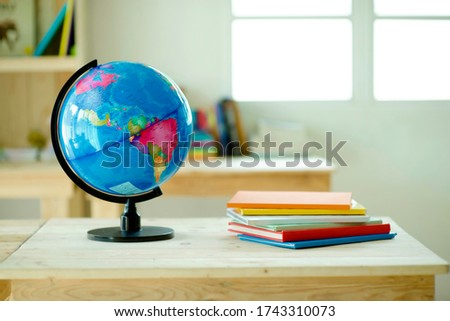 Globe on desk.Pinewood table.Shelves with colorful books.Background.Planet Earth and map.Geography lesson. Stockfoto ©
