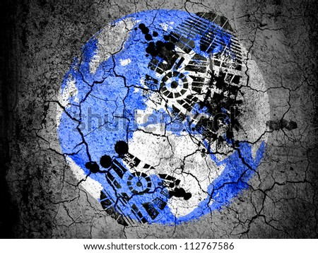 Globe painted on  cracked ground with vignette with dirty oil footprint over it