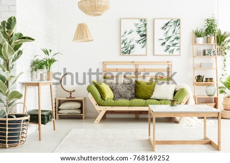 Globe shaped lamp placed on wooden table standing next to green couch in stylish living room interior #768169252