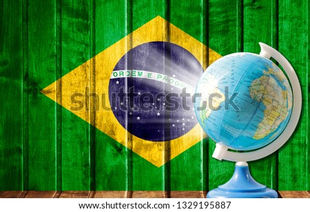 Globe with a world map on a wooden background with the image of the flag of Brazil. The concept of travel and leisure abroad. #1329195887