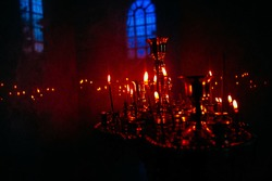 Gloom and candlelight inside the church . Place for praying